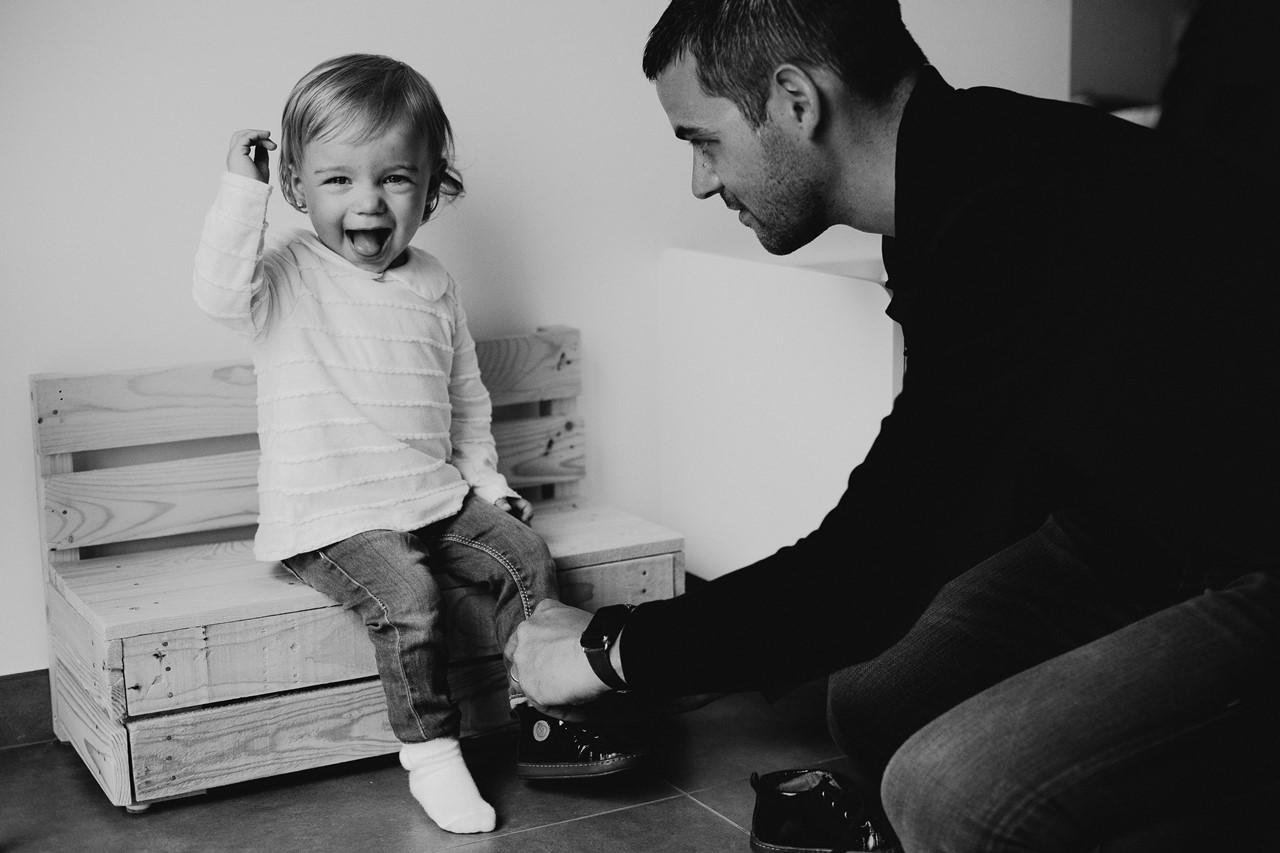 séance famille lifestyle maison papa met chaussures enfant