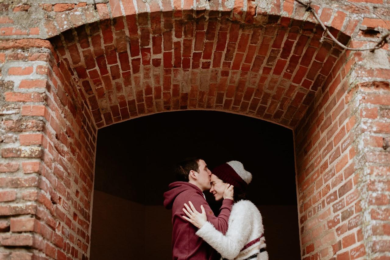Séance engagement Albi futurs mariés bisou front arcades briques