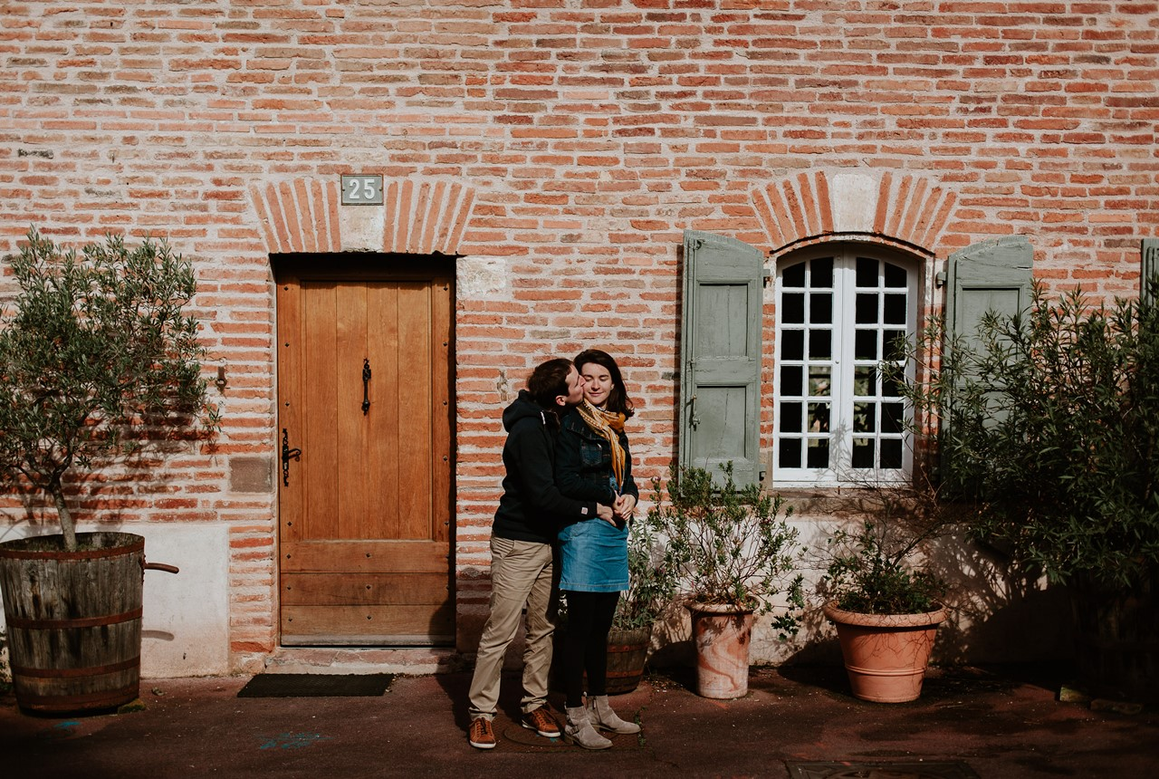 Séance engagement Albi futurs mariés maison briques bisous