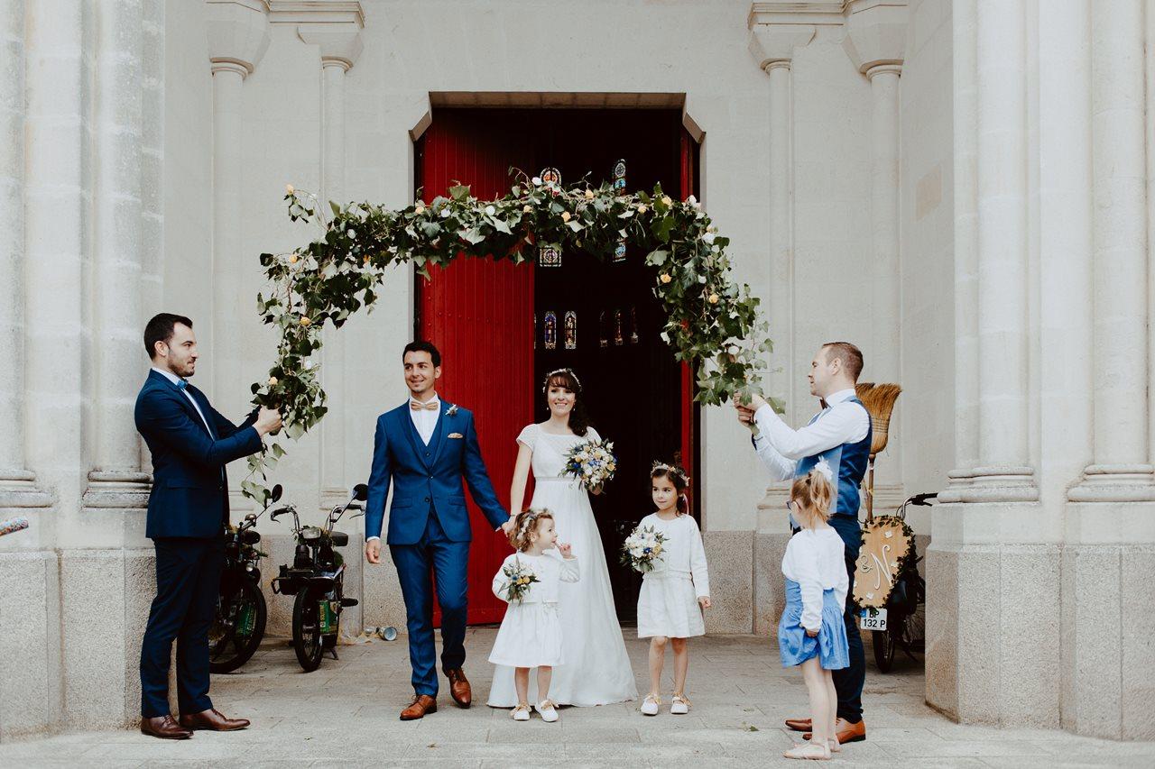 Mariage bohème nantes sortie église mariés arche végétal