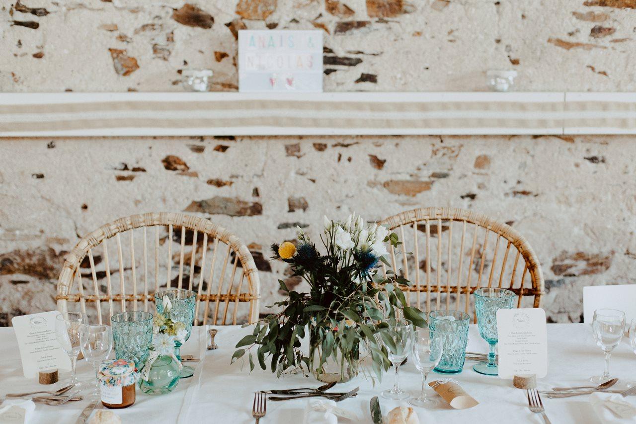 Mariage bohème guermiton table mariés détails mur en pierre chaises en osiers