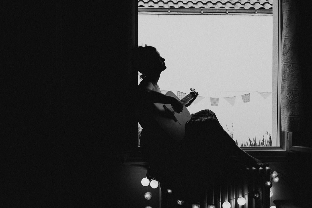 séance portrait femme intimiste fenêtre guitare guirlande lumière noir et blanc