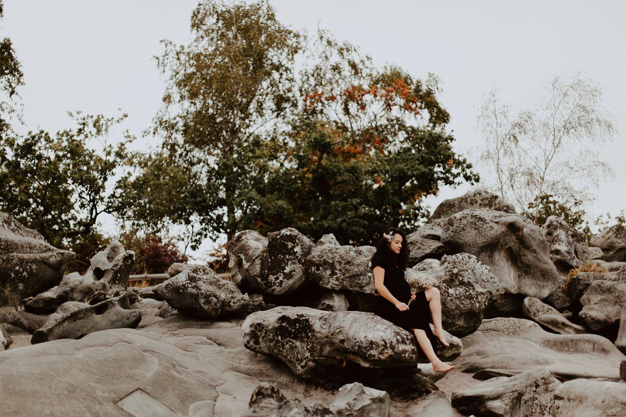 seance-maternité-nature-femme-enceinte-assise-rocher-fleurs