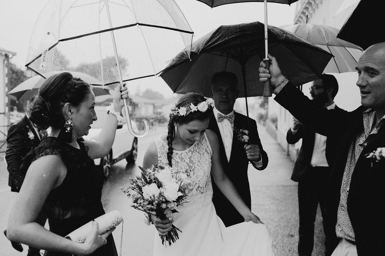 Photo mariage arrivée mariée mairie parapluies noir et blanc