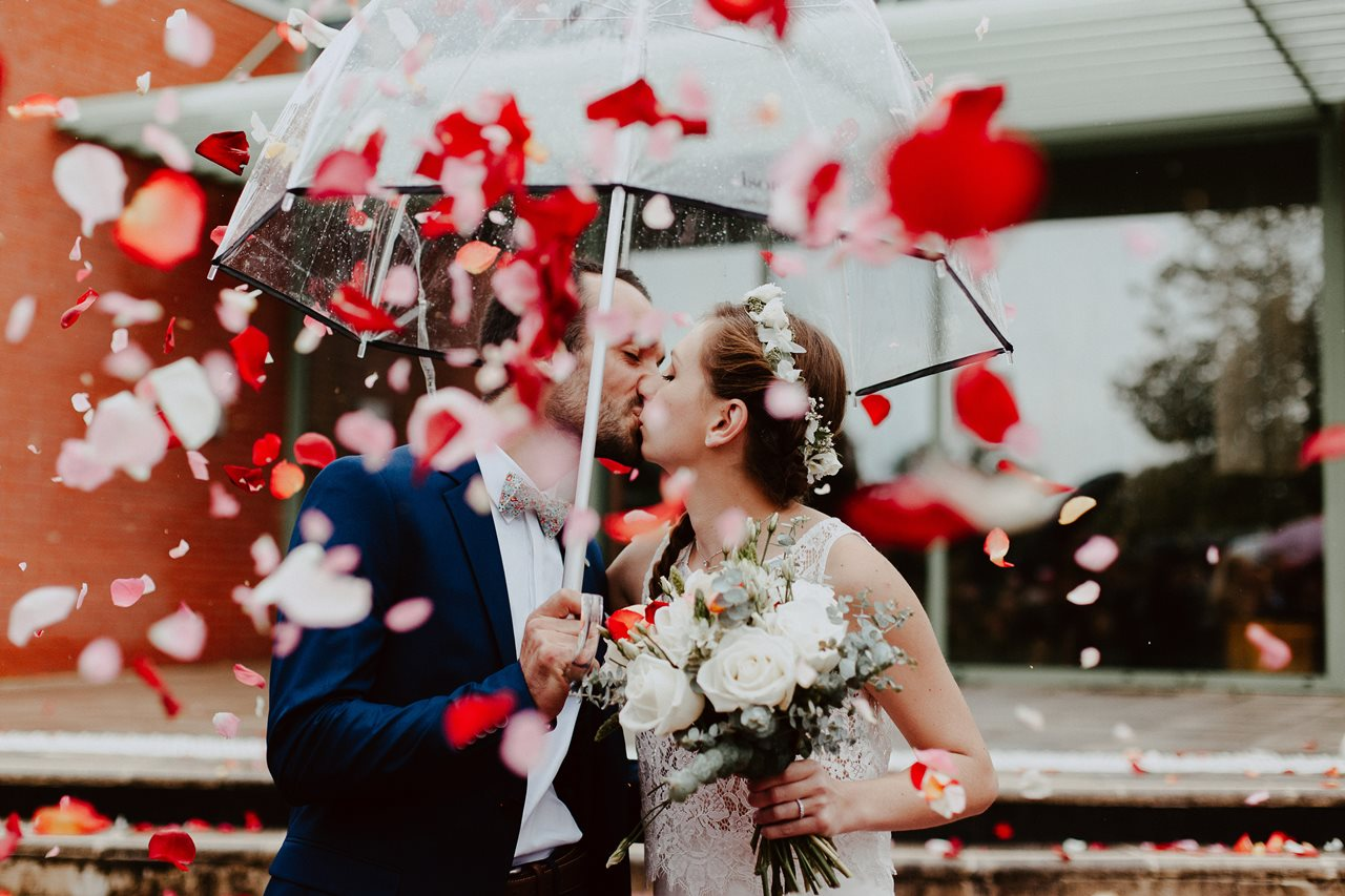 Photo mariage sortie marie parapluie bisou