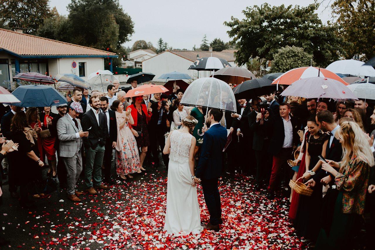 Photo mariage sortie marie mariés invités parapluies