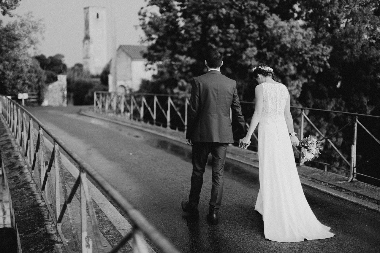 Mariage champêtre photo mariés de dos sur un pont noir et blanc