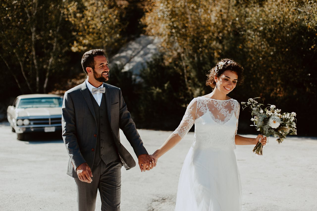 mariage nude désert mariés main dans la main sourire devant voiture buick electra 225