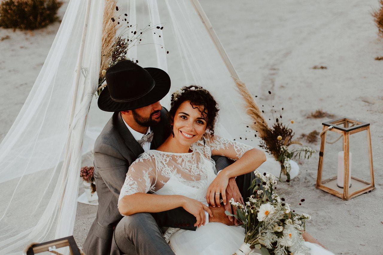 mariage nude plage tipi portrait mariés assis mariée sourire
