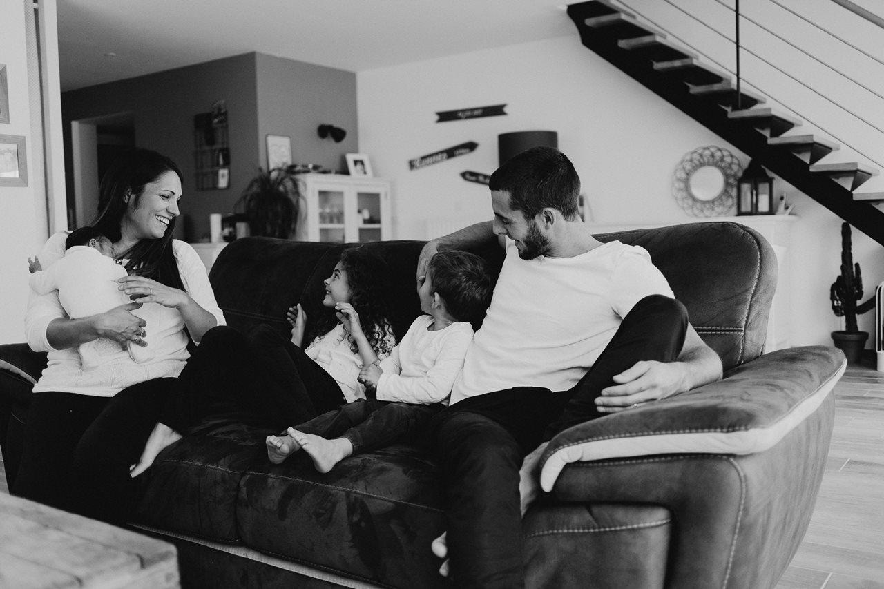 séance nouveau-né lifestyle famille canapé noir et blanc