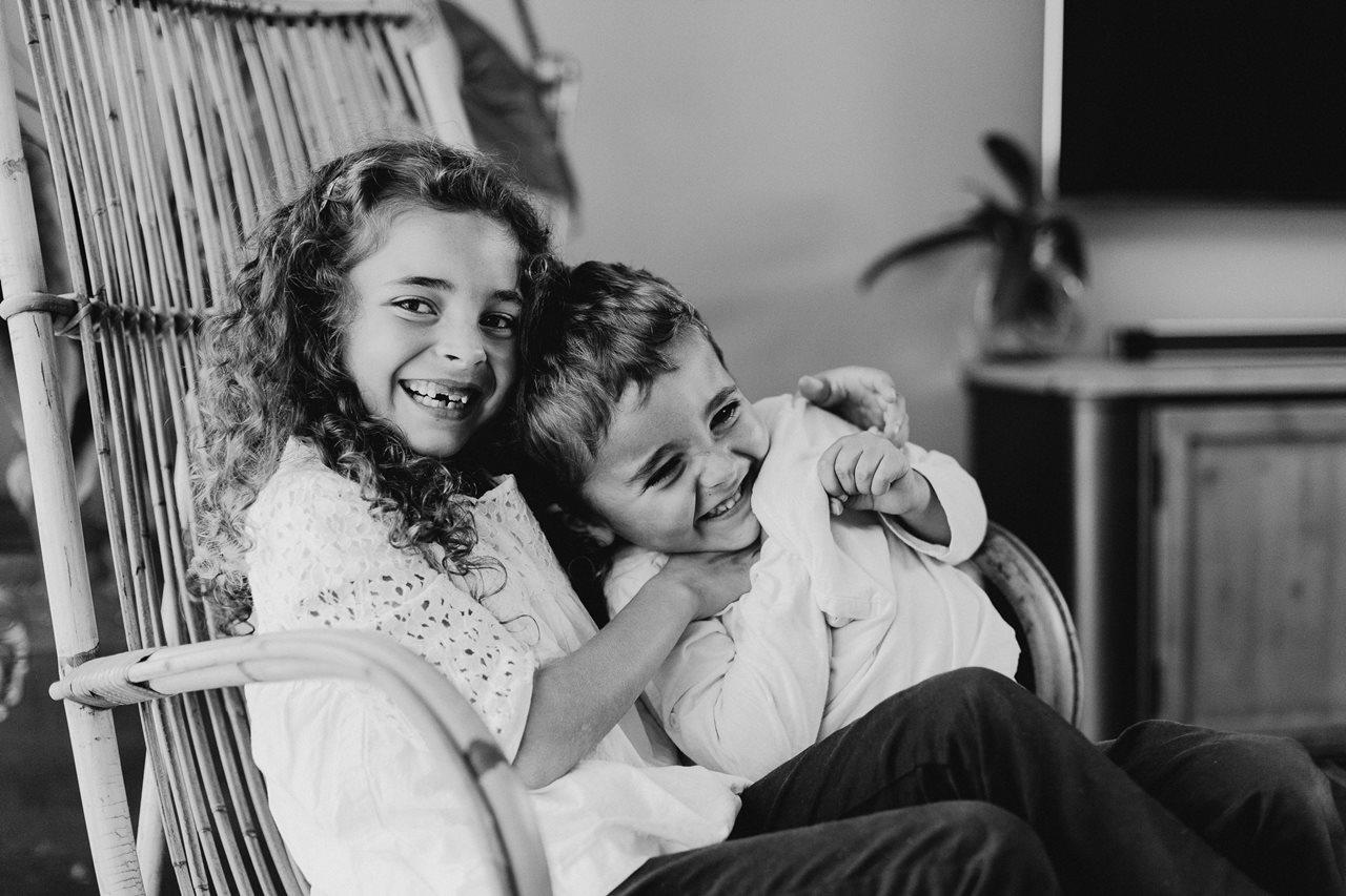 séance famille nouveau-né lifestyle complicité frère et soeur chatouilles noir et blanc