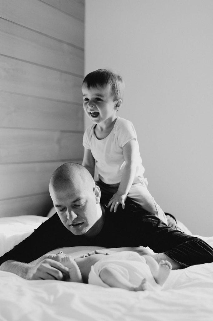 séance nouveau-né lifestyle instants jeux et calîn papa enfants noir et blanc