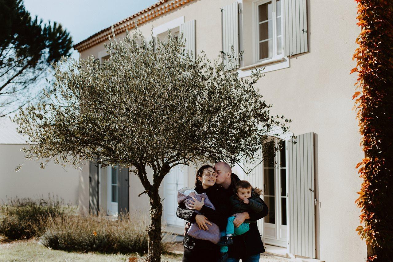 séance nouveau-né lifestyle portrait famille devant la maison bisou parents