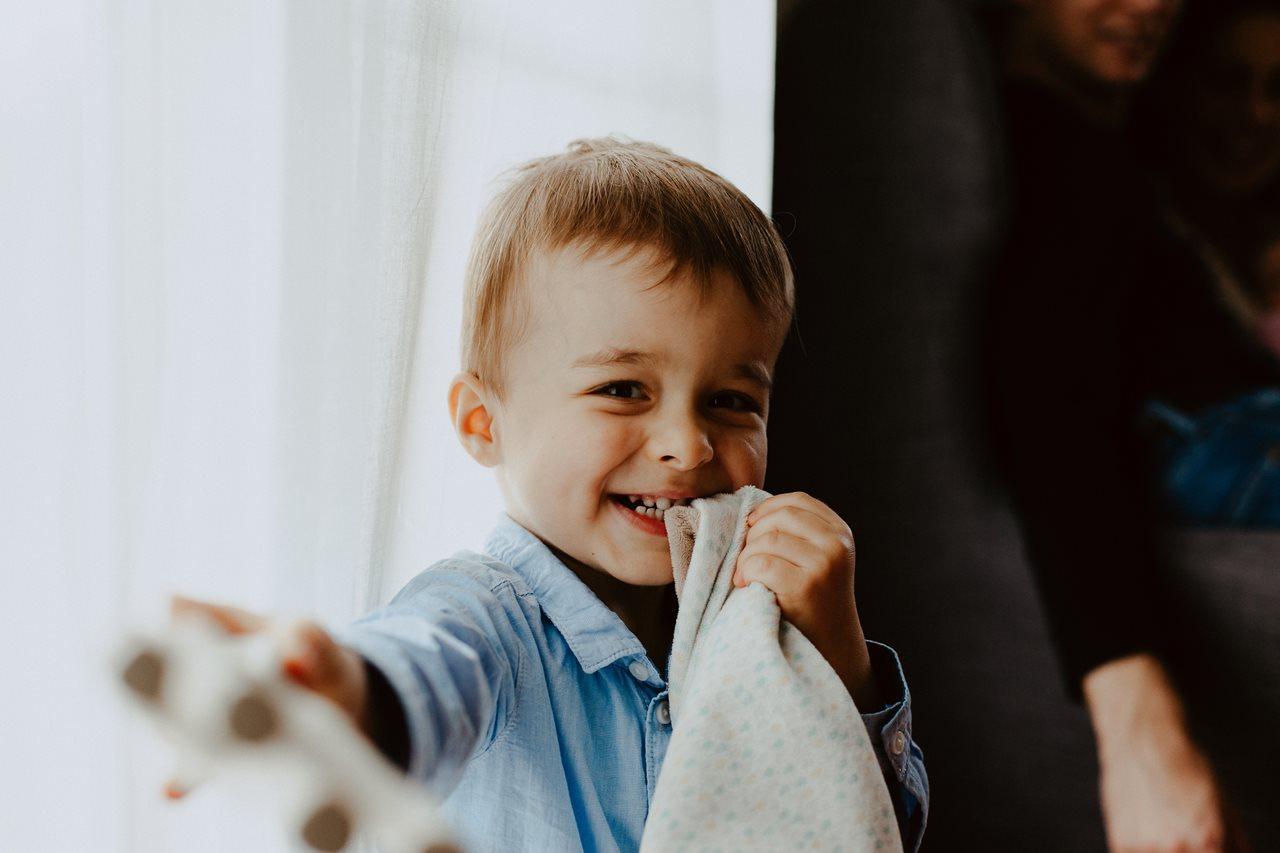 séance nouveau-né famille lifestyle portrait petit garçon fenêtre rires doudou