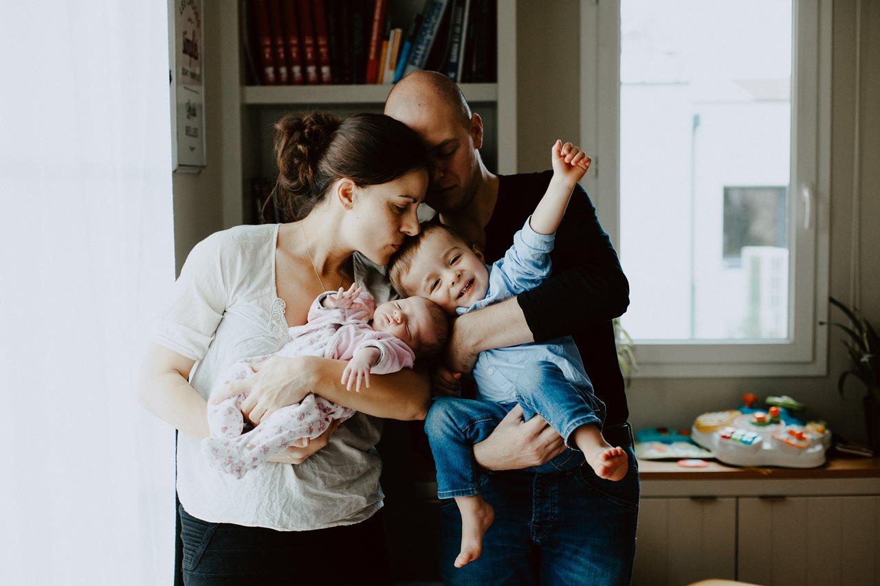 séance nouveau-né lifestyle portrait famille calîn parents bébé et petits garçon joie de vivre
