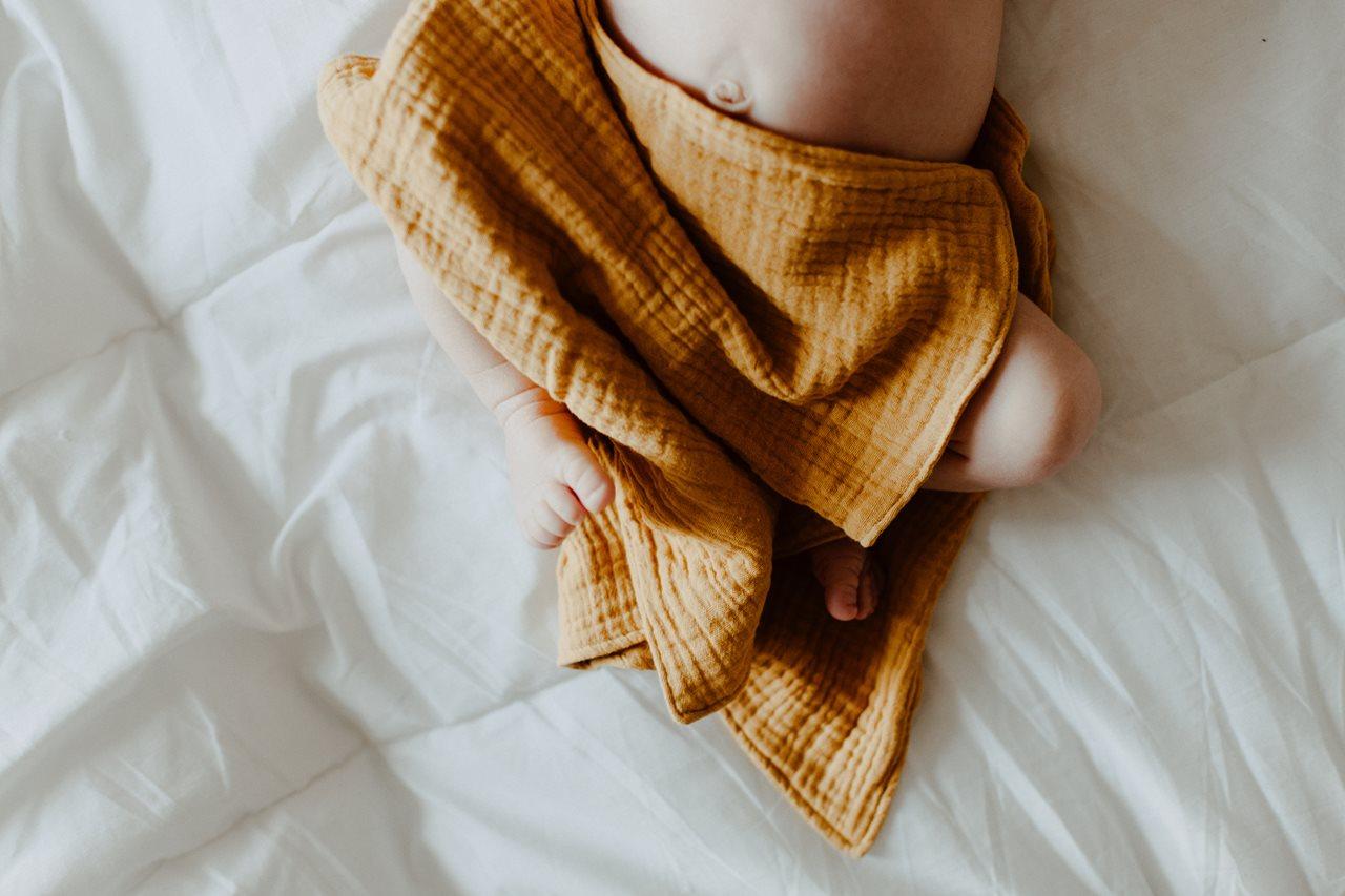 séance nouveau-né lifestyle jambes nues bébé lit