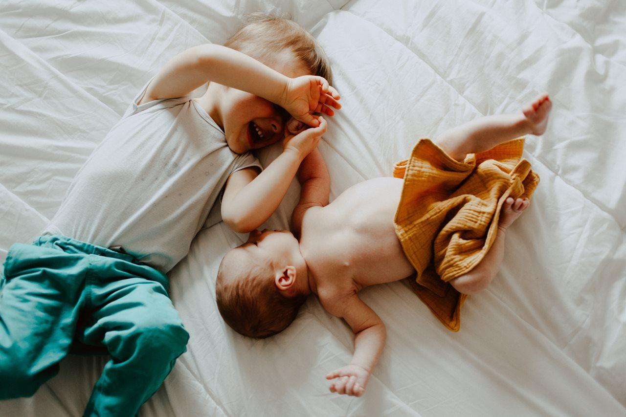 séance nouveau-né lifestyle frère et soeur calin lit