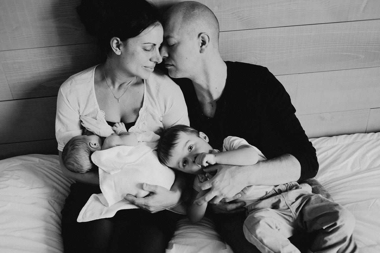 séance nouveau-né à la maison calin famille lit noir et blanc
