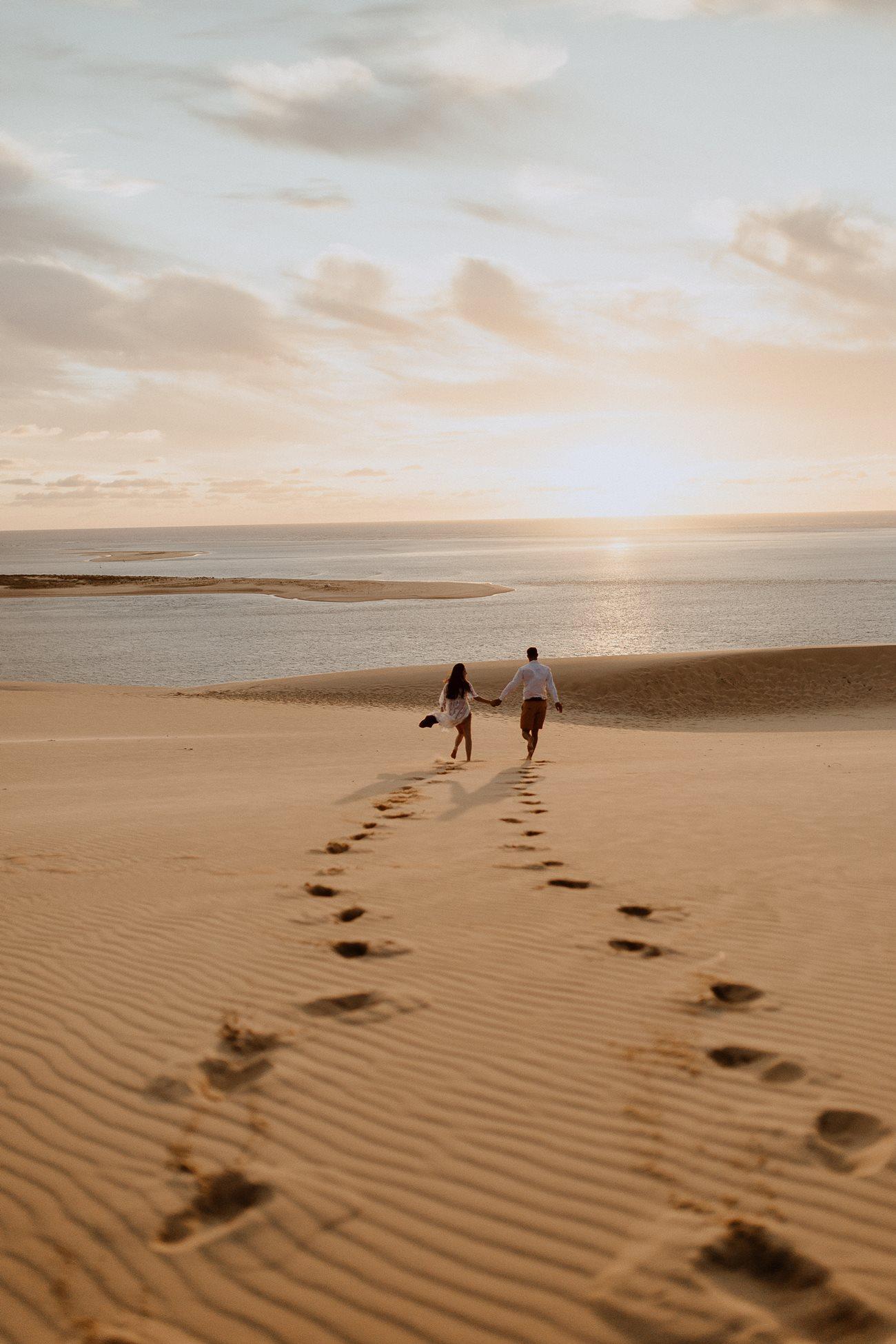 séance couple dune du Pilat mariés qui courent pieds nus dans le sable