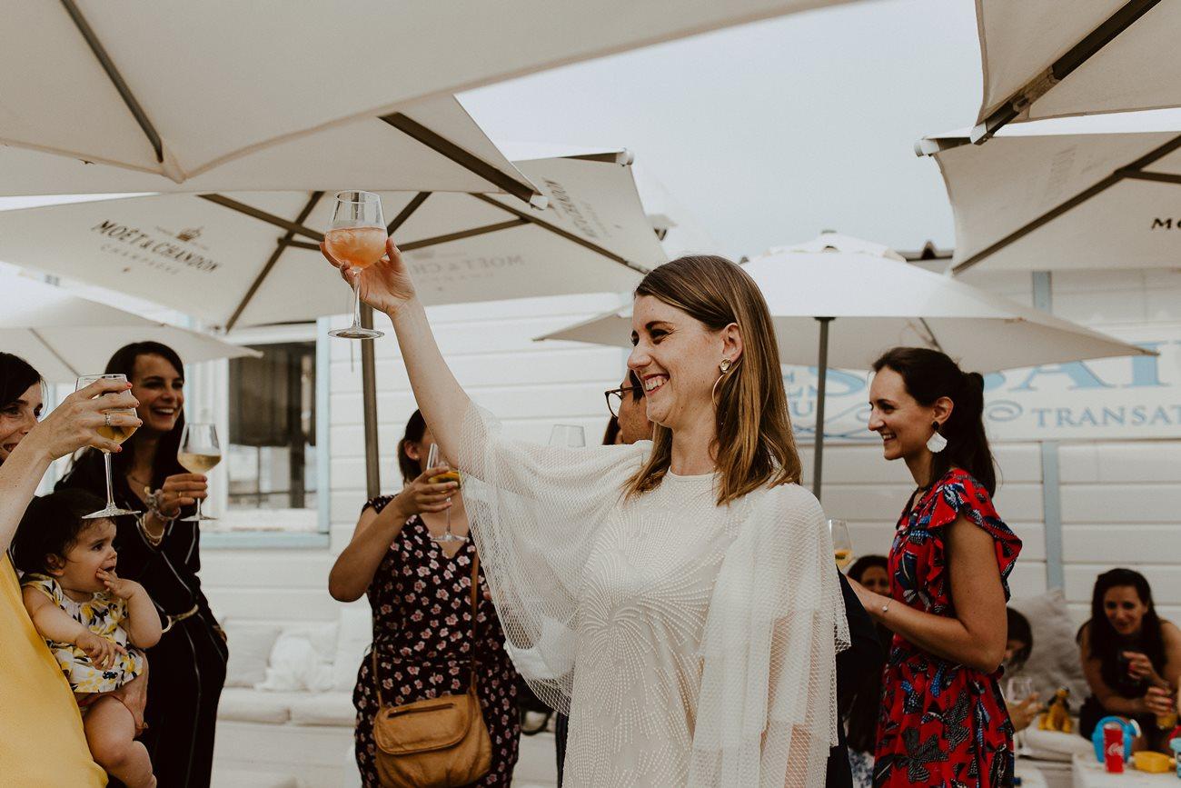 Mariée cocktail mariage trinque invités sourire plage été