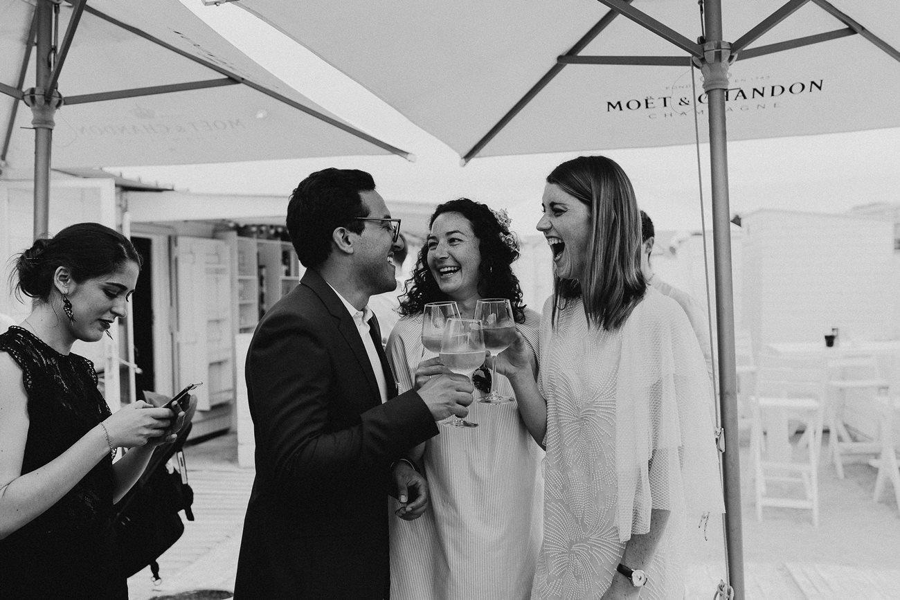 Mariés trinquent cocktail mariage plage rires noir et blanc