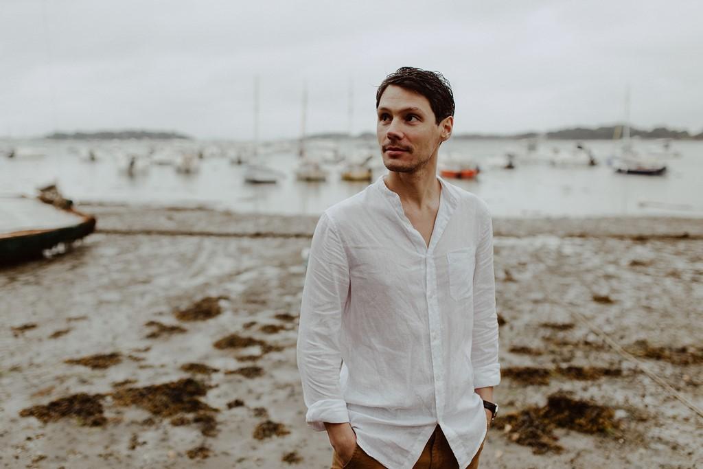 portrait homme plage mer bateaux ciel gris